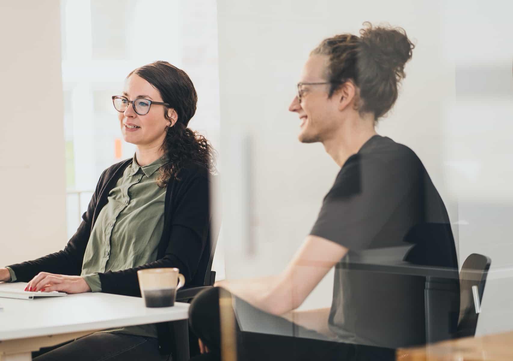 Tina und Nik bei der Arbeit am Schreibtisch