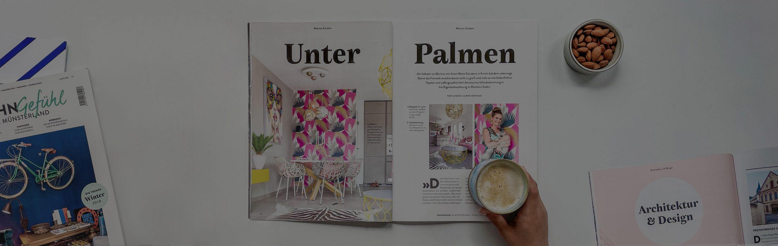 Aufgeschlagene Magazine mit Kaffee und Nüssen daneben und darüber