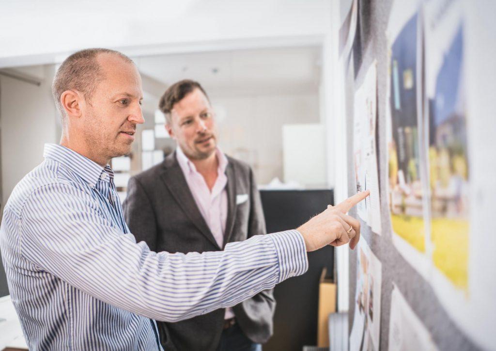 Lars Wentrup und Christoph Wüllner besprechen den aktuellen Stand eines Magazins an einer Pinnwand