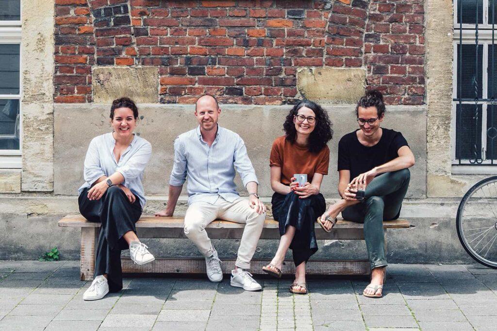 Teamfoto auf einer Bank vor dem Bürogebäude